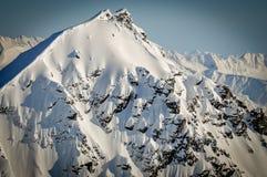 Parte superior coberto de neve íngreme da montanha, Alaska Imagem de Stock