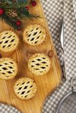 A parte superior da estrutura tritura tortas em uma placa de pão de madeira para o Natal Imagens de Stock