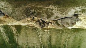 Parte superior da inclinação branca alta do penhasco com pedras e parte inferior do penhasco coberto com a grama verde tiro Vista video estoque