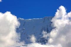 Parte superior da montanha flanqueada por nuvens Imagem de Stock