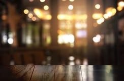 Parte superior da tabela de madeira com barra do borrão ou fundo escuro da noite do partido da cidade da luz do bar foto de stock royalty free