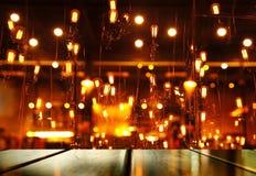 Parte superior da tabela de madeira com luz do borrão - lâmpada alaranjada da barra ou do bar para imagem de stock royalty free