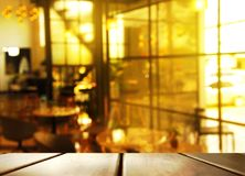 Parte superior da tabela de madeira com luz da manhã do borrão da janela de vidro no caf imagem de stock