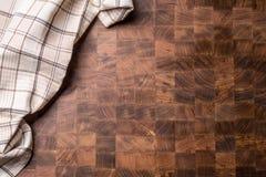 Parte superior da toalha de mesa quadriculado da vista na placa de carniceiro de madeira vazia fotografia de stock
