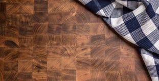 Parte superior da toalha de mesa quadriculado da vista na placa de carniceiro de madeira vazia fotos de stock