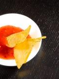 Parte superior da vista de nachos torrados do milho com molho de tomate quente picante como um petisco ou um aperitivo em um disc Imagens de Stock