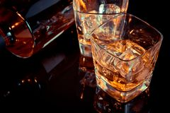 Parte superior da vista do vidro do uísque perto da garrafa na tabela preta com reflexão, estilo antigo Fotos de Stock