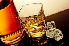 Parte superior da vista do vidro do uísque perto dos cubos da garrafa e de gelo na tabela com reflexão Imagens de Stock