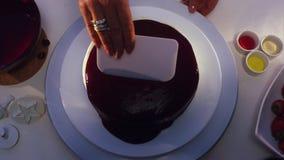 Parte superior de creme smoothering do bolo da mão do ` s da mulher com o cartão plástico quadrado liso branco filme