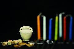 A parte superior de giro, o potenciômetro do óleo, as moedas douradas e as velas são símbolos de J Fotografia de Stock Royalty Free