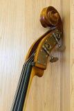 A parte superior de uma garganta do violoncelo inclina-se em uma parede de madeira Imagem de Stock Royalty Free
