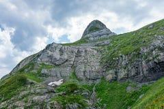 A parte superior de uma montanha com neve e inclinações rochosas foto de stock royalty free