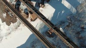 A parte superior disparada aérea disparou de um trem que cruza uma ponte sobre o rio da montanha no dia de inverno ensolarado vídeos de arquivo