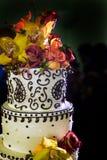 A parte superior do bolo de casamento cobriu com flores brilhantes imagens de stock