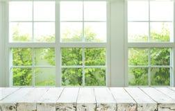 Parte superior do contador de madeira da tabela no fundo do jardim da opinião da janela do borrão imagens de stock