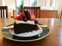 Parte superior líquida do queijo do bolo de chocolate com a baga da mistura com fundo do borrão, tempo do chá Fotografia de Stock