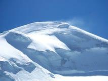 Parte superior nevado da montanha no vento Imagens de Stock Royalty Free