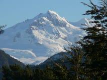 Parte superior Snow-covered da montanha na luz do sol Fotografia de Stock