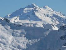 Parte superior Snow-covered da montanha na luz do sol Fotografia de Stock Royalty Free