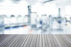 Parte superior vazia da tabela de madeira e borrada do fundo do gym da aptidão fotografia de stock