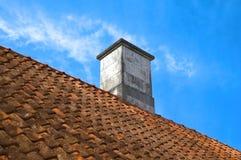 Parte superiore coperta di tegoli del tetto con il camino Fotografia Stock