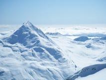 Parte superiore della montagna sopra le nubi Immagine Stock