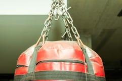 Parte superiore di borsa di perforazione rossa di pugilato con il primo piano delle catene Immagine Stock Libera da Diritti