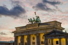 Parte superiore di tor di Brandenburger a Berlino con la luce rosa di sera e le nuvole molli, inverno, Germania Fotografia Stock