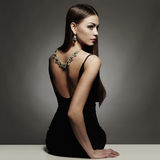 Parte traseira bonita da jovem mulher em um vestido 'sexy' preto menina da beleza com uma colar nela para trás Fotos de Stock Royalty Free
