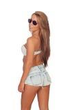 Parte traseira bonita sensual da menina com as calças de brim curtos e os óculos de sol Imagens de Stock