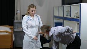 Parte traseira de exame do ` s do homem do fisioterapeuta fêmea na clínica filme