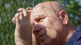 Parte traseira decepcionada da pessoa de uma cerca metálica Stay Sad e impossível foto de stock