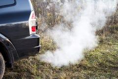 A parte traseira do carro preto com a emissão do fumo da tubulação de exaustão no fundo da natureza fotografia de stock royalty free