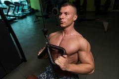 Parte traseira do exercício do homem do músculo da aptidão na máquina imagem de stock
