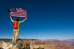 A parte traseira do homem com mochila, bandeira dos EUA, Grand Canyon Imagem de Stock
