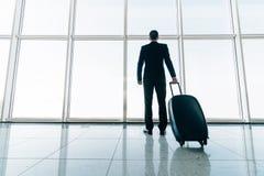 Parte traseira do homem de negócios e da mala de viagem no voo de espera do aeroporto Conceito do curso, conceito das férias de v foto de stock royalty free