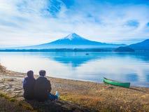 A parte traseira do viajante 30s dos pares de Ásia a 40s senta e vê o lago em Fotos de Stock Royalty Free