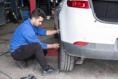 Parte traseira em mudança mecânica do pneu de um carro branco fotografia de stock