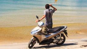 A parte traseira Guy Stands do close up pelo velomotor levanta a mão na praia video estoque