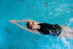 Parte traseira relaxado da natação da menina sobre imagem de stock royalty free