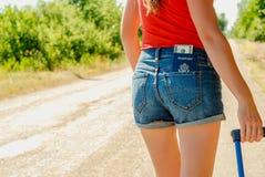 Parte traseira 'sexy' do ` s da mulher no short das calças de brim com um passaporte e dinheiro em um bolso na parte traseira foto de stock