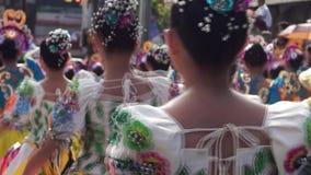 Parte trasera cercana para arriba de bailarines culturales en diversa danza del traje del coco a lo largo de las calles para cele metrajes