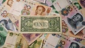 Parte trasera de un dólar americano entre el chino Yuan Renminbi Banknotes imagen de archivo