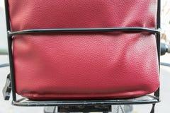 Parte trasera del asiento del bebé en la bicicleta hecha por el cuero rojo Imagen de archivo libre de regalías