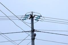 Parte uma de uma coluna concreta cinzenta com fios pretos contra o céu imagens de stock
