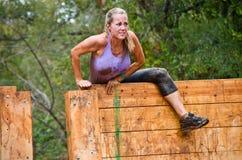 Partecipante della corsa del fango che si arrampica sopra un ostacolo Immagine Stock