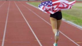 Partecipante di sport da U.S.A. che celebra vittoria e funzionamento sull'arena, successo video d archivio