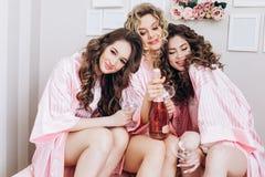 Partei f?r M?dchen Freundinnen trinken rosa Champagner vor der Heiratszeremonie in den rosa Pyjamas stockbilder
