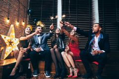 Partei mit Freunden Glückliche tragende Wunderkerzen der jungen Leute und ha Stockfotos