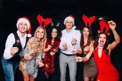 Partei mit Freunden Sie lieben Weihnachten Gruppe nettes tragendes Wunderkerze- und Sektkelchtanzen der jungen Leute lizenzfreie stockfotografie